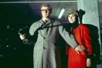 HARRY PALMER (MICHAEL CAINE) SHIELDS JEAN (SUE LLOYD) AS HE HOLDS A MACHINE GUN)